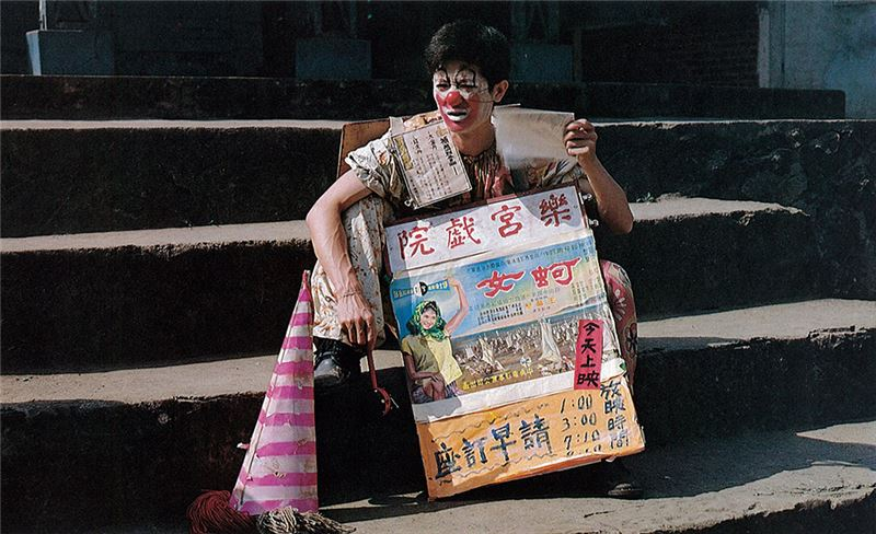 His job is to roam up and down the streets and alleys of a small town in Chiayi County all day long to advertise new films.