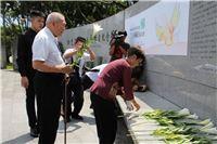 1950年代政治受難者張常美女士(中)、蘇玉鑑先生(左)手持臺灣百合向白恐紀念碑亡靈致意。