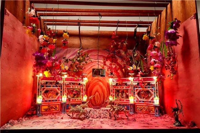 張徐展作品〈紙人展–房間〉,暗紅色的祭壇中蜷曲著一隻紙偶-小黃,走獸們圍繞著跳舞,是慶祝還是哀悼,一如生命的糾結與怪誕的情緒。