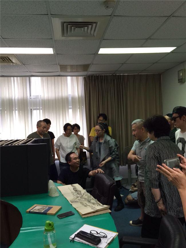 胡恩威老師(中蹲者)與《十八羅漢圖》創作團隊討論設計概念。(林雅惠拍攝,胡恩威提供)