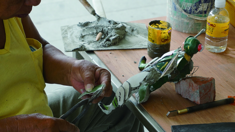 在剪黏工程現場,可以看到師傅重複著拿瓷片向灰泥胚體比對的動作。原來「剪」需要在瓷碗上劃一刀、再用手一扳、加上鉗子不斷地修剪,才能形成一尊泥塑人偶的一塊小小衣角。.JPG