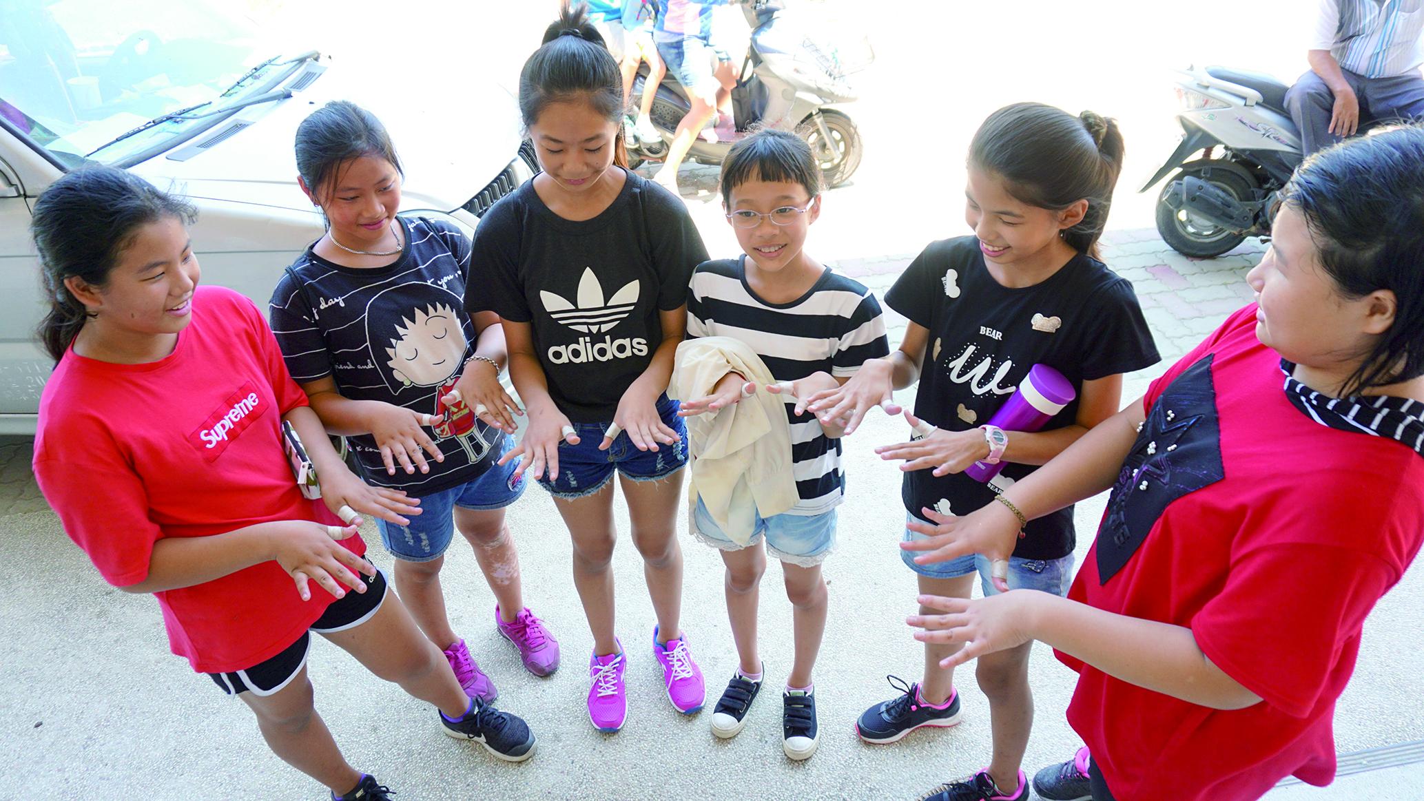 圖7吳登興表示,練習用的獅頭挺重,他會買膠布保護這些孩子。這些學生私下抱怨吳登興很兇,其實他也有著鐵漢柔情。.JPG