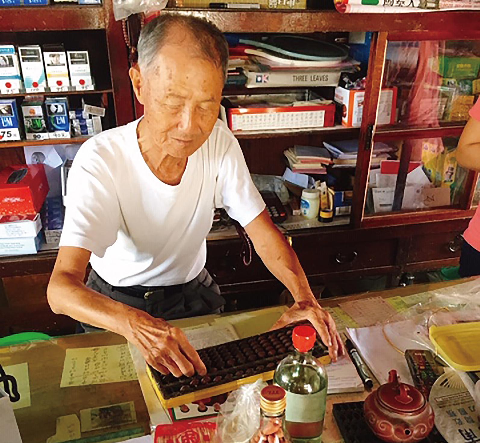 第二代經營者張錦運熟稔地使用算盤幫顧客計算金額。-01.JPG