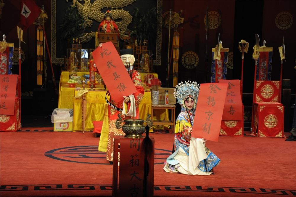 《加官晉爵》男加官頭戴面具,身穿蟒袍,女加官則鳳冠霞帔,男、女加官展示條幅上的吉祥語,增添新春喜氣。