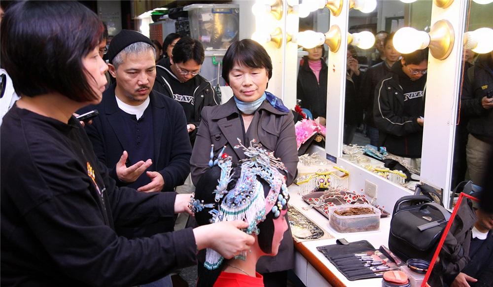李小平導演向龍部長介紹京劇旦角演員包頭的過程,圖中演員完成貼片子用來修飾臉型並以點翠裝飾