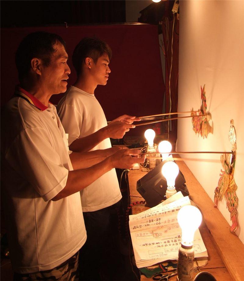 張榑國團長與兒子張智絢於後台聯手操作皮影偶戲。