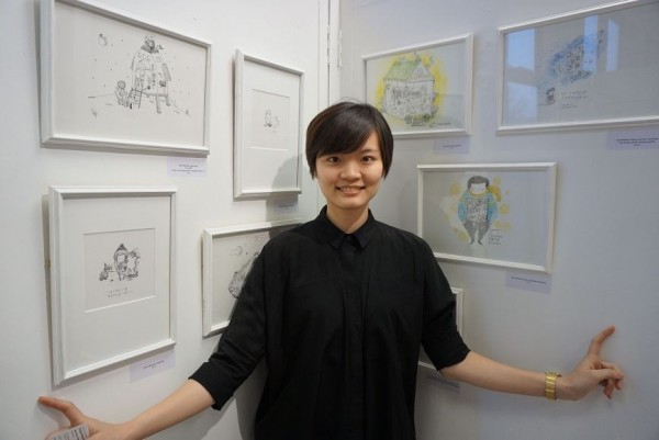 Taiwanese painter Klara Huang poses with illustrations depicting her observations on Taiwan's recent surge in youth activism.