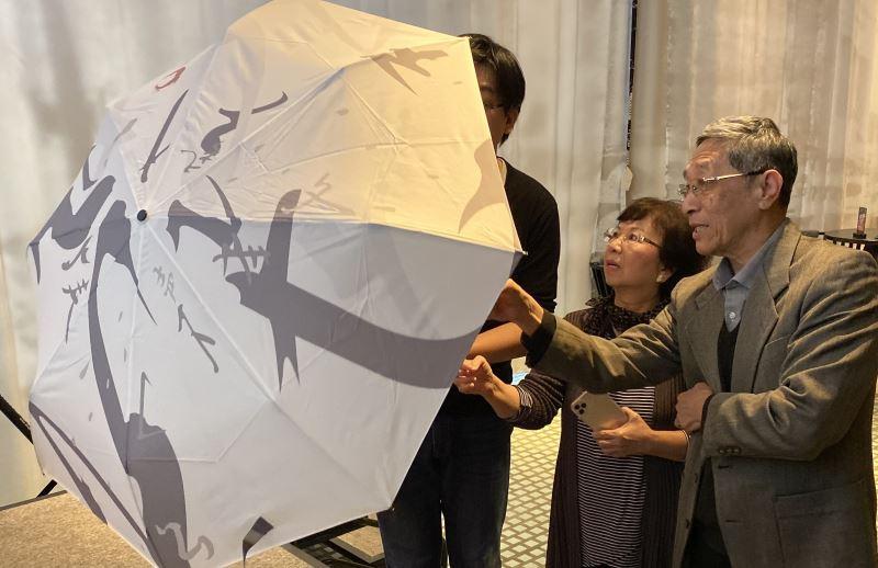 賴和家屬賴悅顏及夫人葛麗姝觀賞以賴和漢詩所設計的傘款