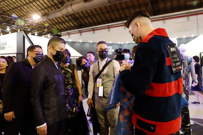 參展品牌設計師向文化部長李永得介紹服飾的布料材質及背後的創作靈感。