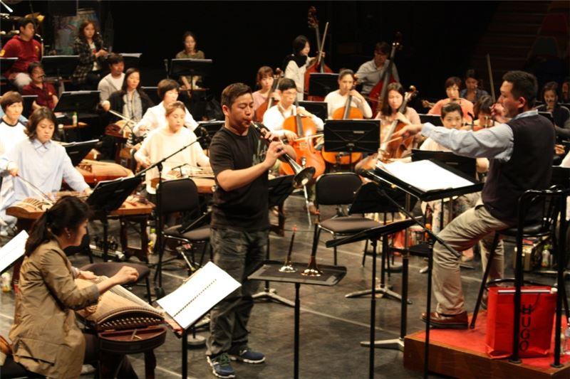 指揮顧寶文老師與韓國國立國樂管弦樂團及本團獨奏家石瑞鴻老師(嗩吶)進行排練