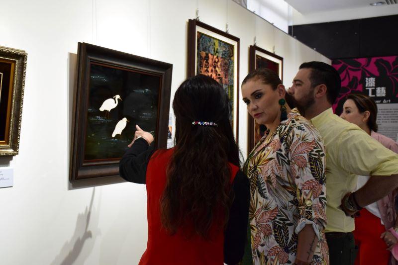 照片3、瓜地馬拉民航局局長伉儷專注聆聽解說人員介紹駐園工藝師李麗卿的漆藝作品