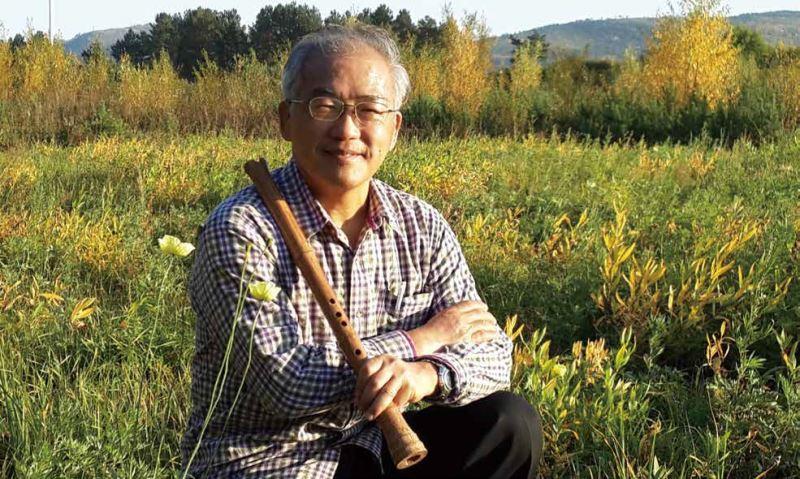吹笛人手握笛子融合在大自然。