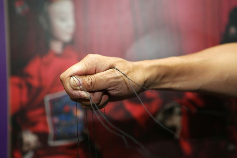操偶基本理線技法有鉤線、拉線、壓線、夾線、挑線等,圖為壓線的手部動作。
