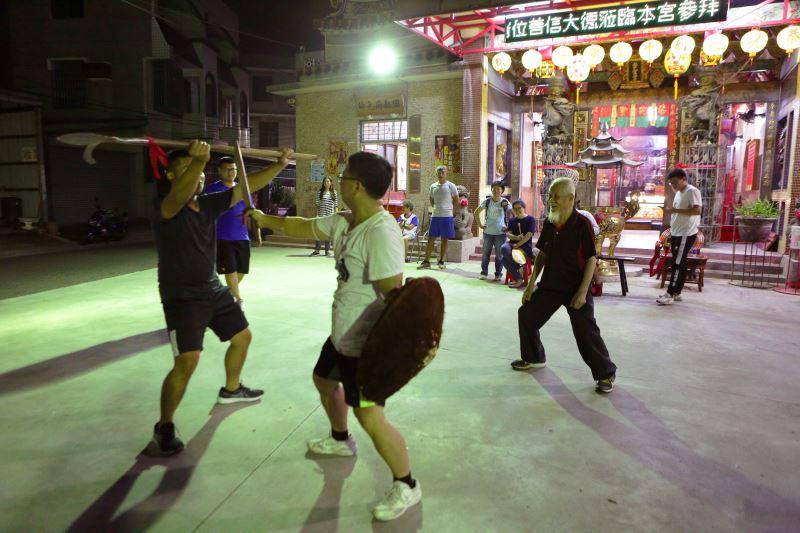在安南外塭崇聖宮廣場前,何國昭正指導當地宋江陣的演練。