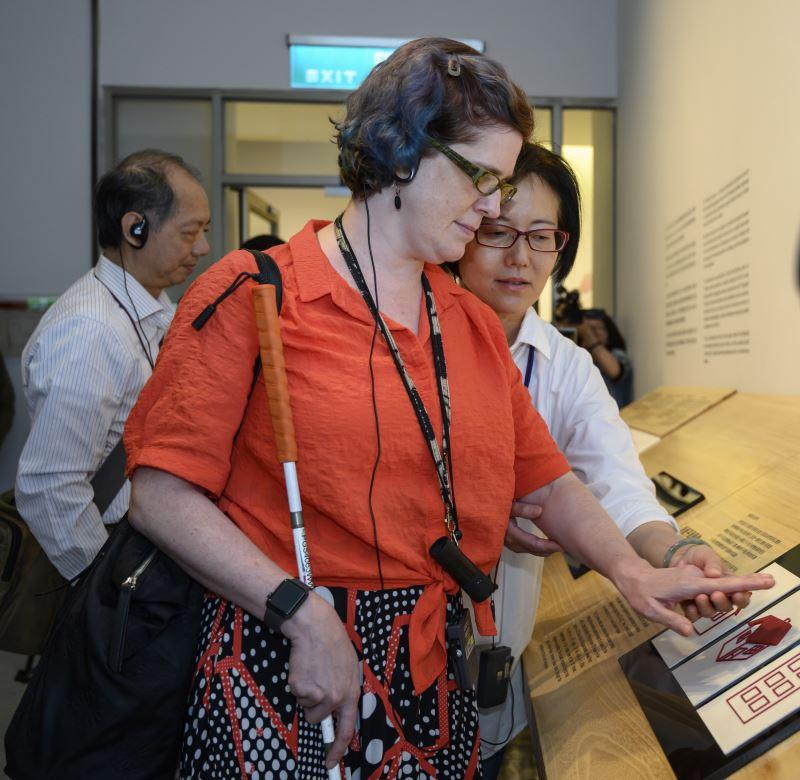 來自紐約的視障藝術家博物館教育人員 Annie Leist由國美館人員陪同邊聽口述影像導覽邊操作輔具,以理解輔具所欲傳達的水彩畫色彩推疊效果