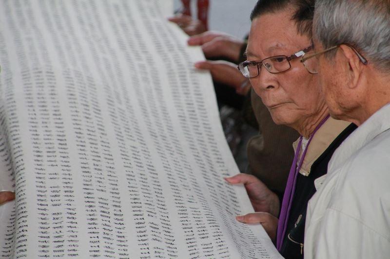 圖4__政治受難者郭金華(左二)、徐文贊(左一)在公告刑事判決有罪撤銷公告儀式中,仔細檢視自己及其他難友們的名字,追憶長達半世紀的白色恐怖苦難歲月。