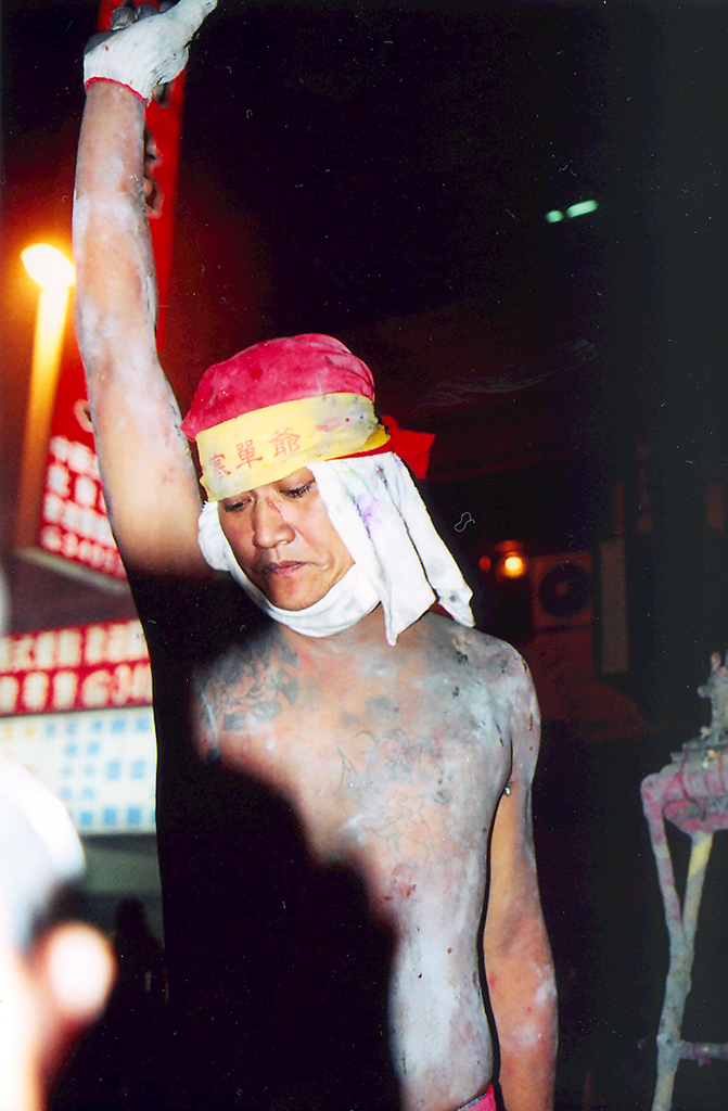 "In Taitung, eastern Taiwan, a group of gangsters serve as the faces of the god Handan during Lantern Festival. For their evening ""god patrols,"" they strip to the waist and ascend a sacred palanquin wearing only masks and red shorts, summoning the local residents and believers to assault and singe their bodies with fireworks."