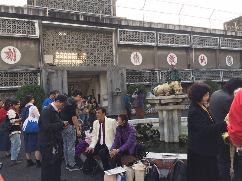 受難者前輩陳深景先生(著白色西裝)於獬豸水池前接受台灣新生報記者王先國採訪