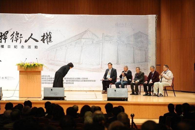 Culture Minister Lung Ying-tai (left) bows to the surviving political victims to show her respect and to thank them for donating their precious belongings to the cause of educating the next generation.