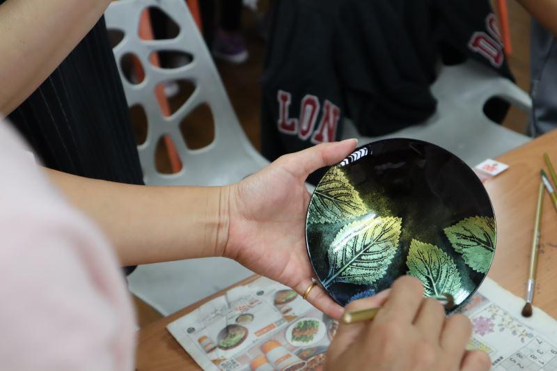 03-同學在漆半乾後,以乾筆掃上金粉。