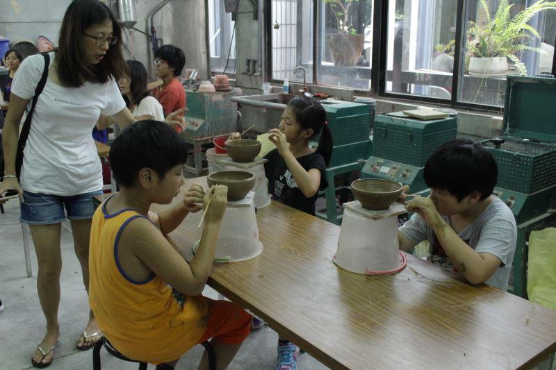 新二代聚精會神進行陶碗表面裝飾