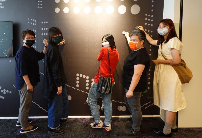 藝術家與作品互動牆〈旅行中的「●_●_●_」〉進行互動