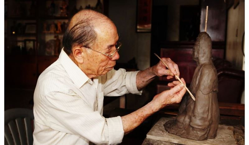 Veteran artisan Shih Chih-hui molds clay over his wooden Buddha statue.