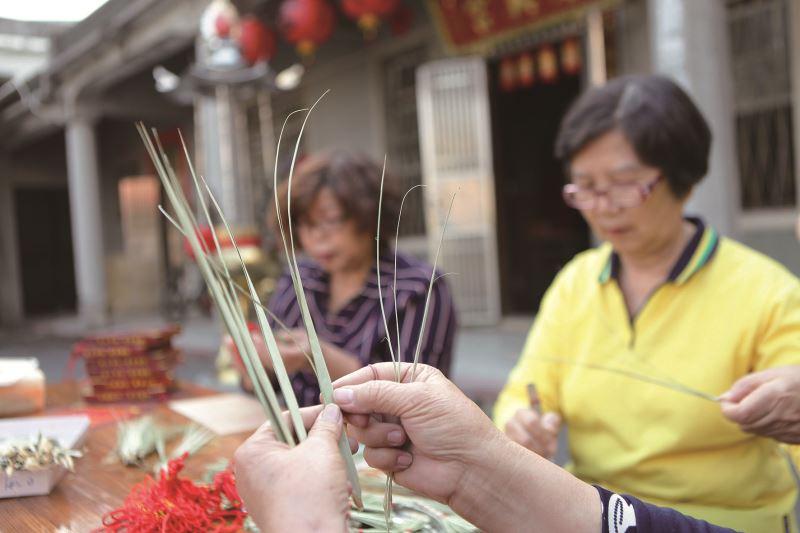 張庭瑜示範如何將槺榔葉聚集成束,再以月桃莖梗綁緊。