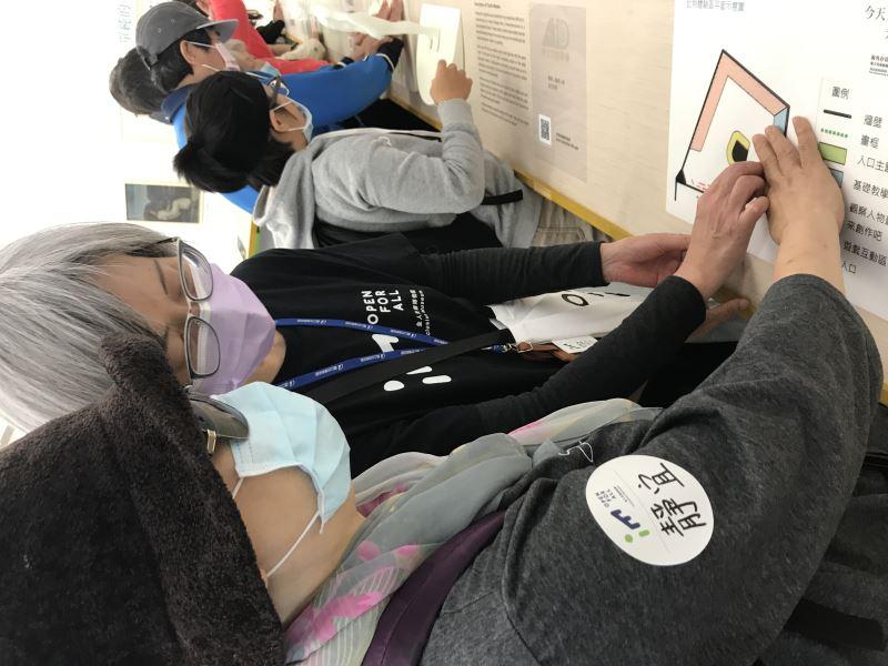 0325場次,志工協助視障者觸摸展場平面圖。