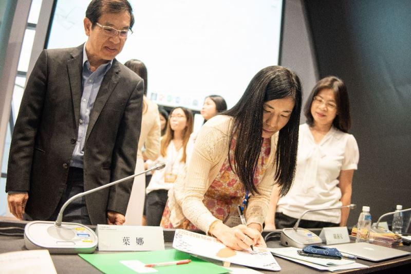 1025香港大學音樂圖書館關燕兒館長於「臺灣音樂策略聯盟」名牌上簽名。左起為臺灣音樂館翁誌聰館主任、關燕兒館長、臺南市立圖書館洪玉貞館長。
