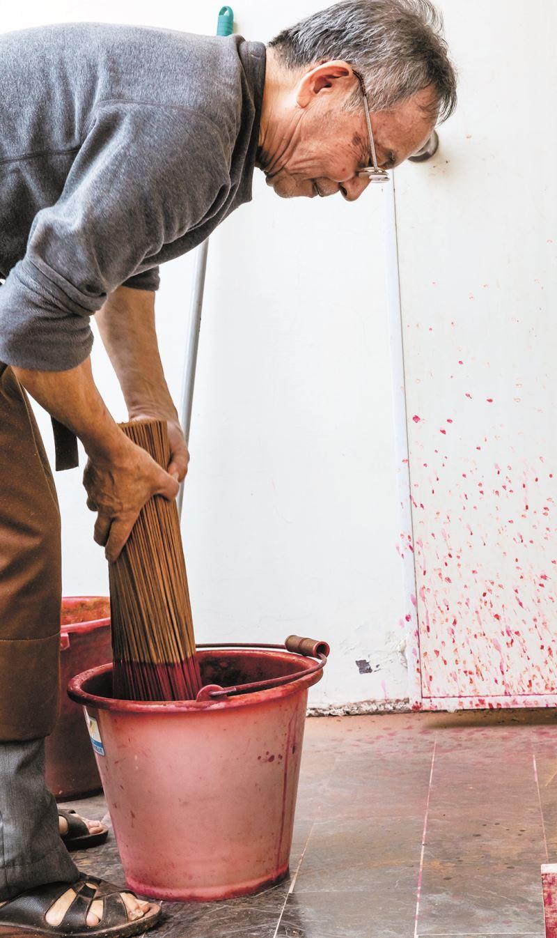 吳博男老師傅將黏好的香浸在顏料中染紅。