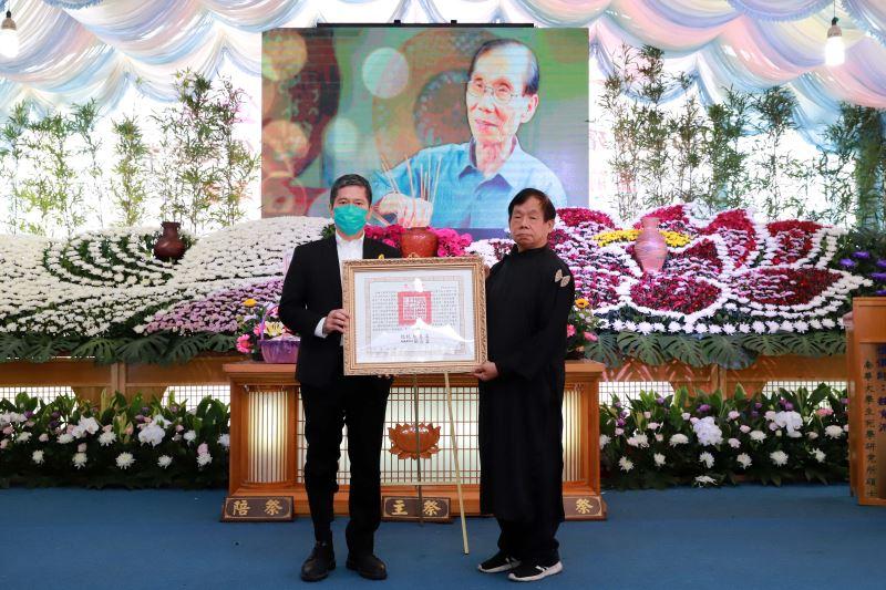 文化部長李永得(左)代表頒贈總統褒揚令,由次子黃啟祥先生代表家屬受贈