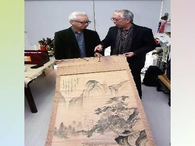 林章湖教授(左)向國父紀念館梁永斐館長介紹其15歲臨摹唐伯虎作品