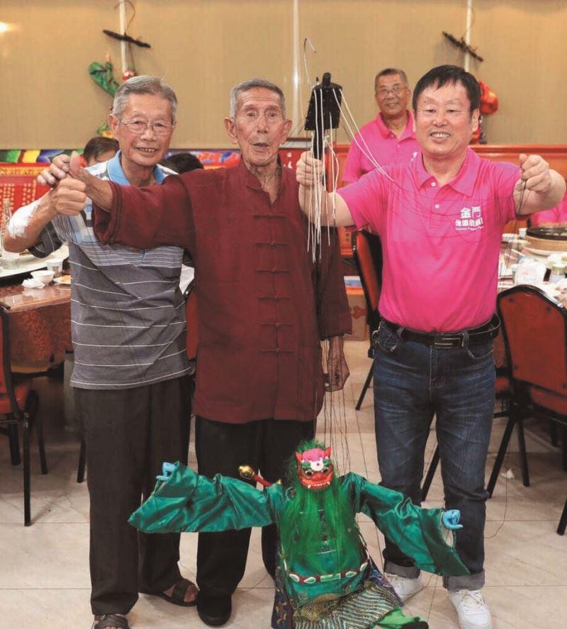 金門傀儡戲劇團蔡甲庚大師(中)榮獲第三屆金門文化獎,於感恩餐會上與泉州傀儡戲大師林文榮(右)合影。
