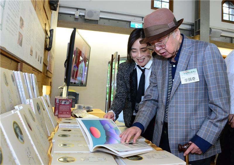 藝術家李錫奇翻閱「家庭美術館─美術家傳記叢書」