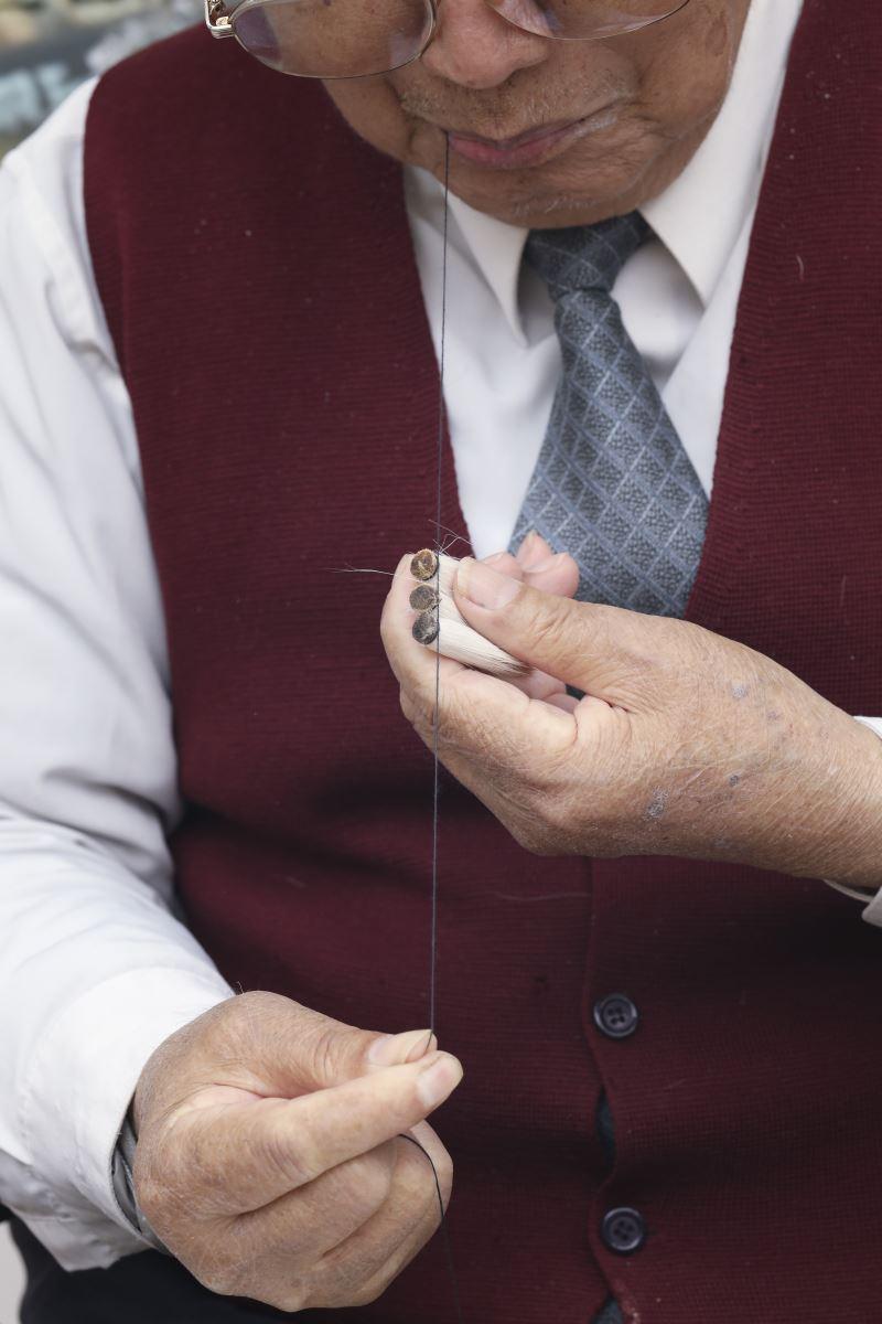 綁筆頭是做毛筆的過程中最為困難的,必須趁筆頭尚未乾燥時,先將線的一端咬住,再用線的另一頭把毛筆頭纏起來綁緊,一條線一次可以綁十幾個筆頭。