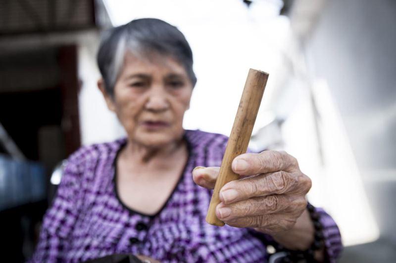 竹占使用的竹管大約長十五公分,是與祖靈溝通的重要器具;圖為簡金美(Rabay Lowbing)手黏竹管。