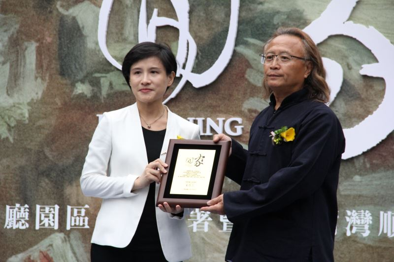 Minister Chen presents Director Chen with a certificate of appreciation.