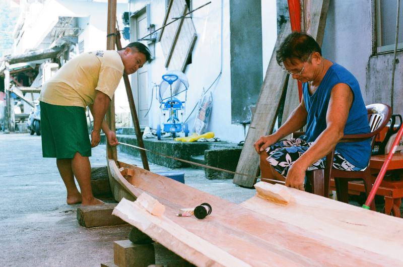 粗胚移到山下後即可進行細修;圖為張世凱與父親張馬群替拼板舟進行細修。