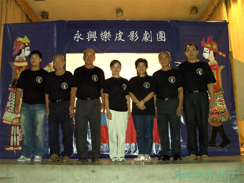 A group picture of Yung Shing Le Shadow Puppet Theatre Troupe in Hungary (2006) (Left to right: Assistant Puppeteer Zhang Xin-hong, Director Zhang Suei, Drummer Zhang Zhen-chang, Adminstrator Zhang Fan-qi, Troupe Leader Zhang Ying-jiao, Puppeteer Zhang Xin-guo, Hu-xian fiddler Zhang Zhen-sheng)