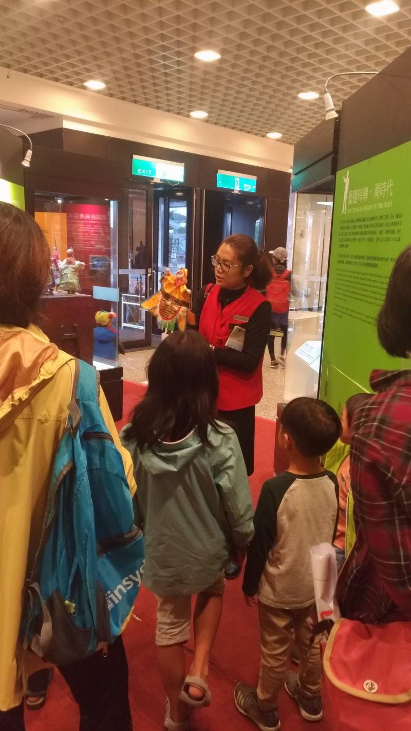 「潮經典。大俠鍾任壁 新興閣布袋戲特展」工作人員向小朋友解說布袋戲的歷史與源流