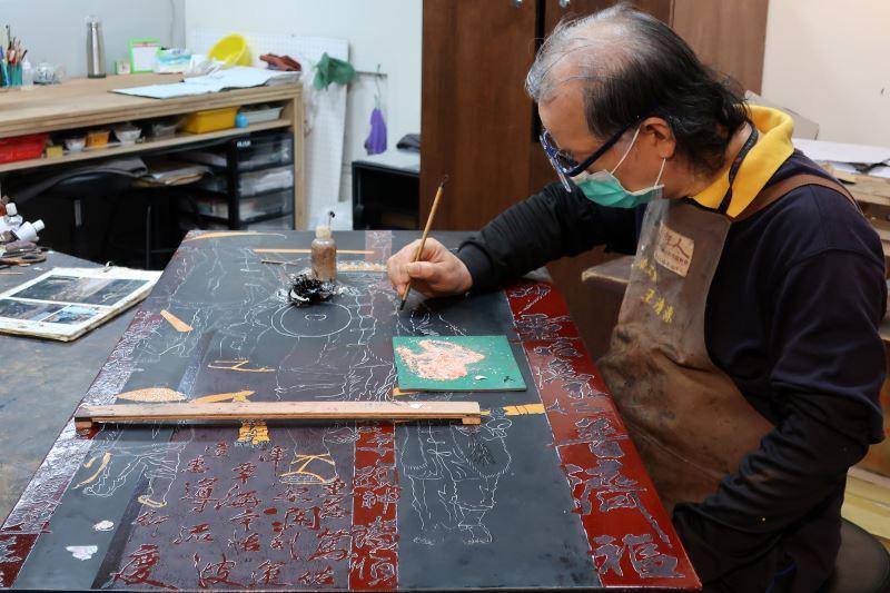 漆工藝師王清源於傳藝工坊內專注漆藝創作。