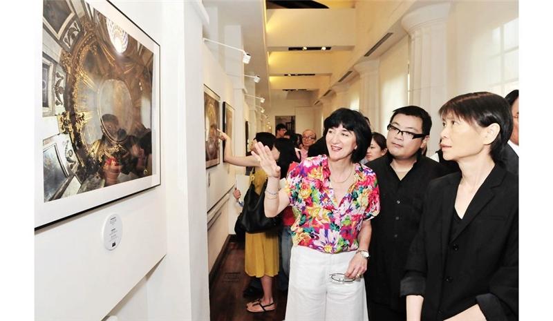 法國攝影師羅蒙女士(左)為總統夫人周美青解說作品