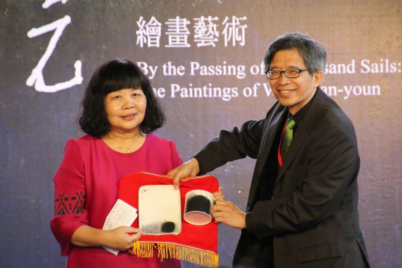 國立歷史博物館館長廖新田(右)致贈以王攀元畫作製成的馬克杯盤組予王攀元女兒王多慈