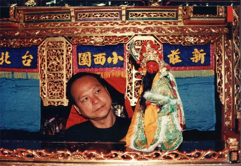 Troupe leader Wang Zhi handling a puppet.