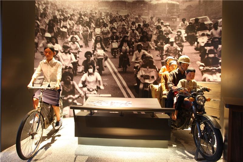 背景中加工出口區上下班擁擠車潮的照片,搭配騎乘自行車的女工與搭載一家5口的野狼機車,說明了工業起飛的狀況下克勤刻苦的臺灣人如何開創「臺灣經濟奇蹟」。