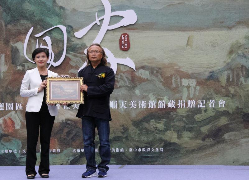 Chen Fei-long, director of the Sun Ten Museum, gifts artist Liao Chi-chun's