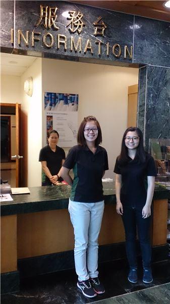 康樂本館服務人員服裝照片(夏裝)。服務人員穿著黑色為主色,兩側側邊有綠色的Polo上衣。