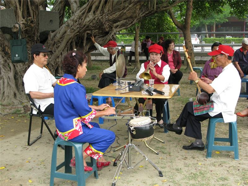 During the performance of the Hakka Ba-yin music, four troupe members sit around a table and play together.