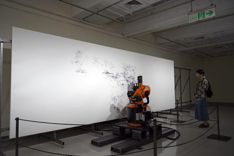 民眾注視著機器手臂「庫卡」創作作品